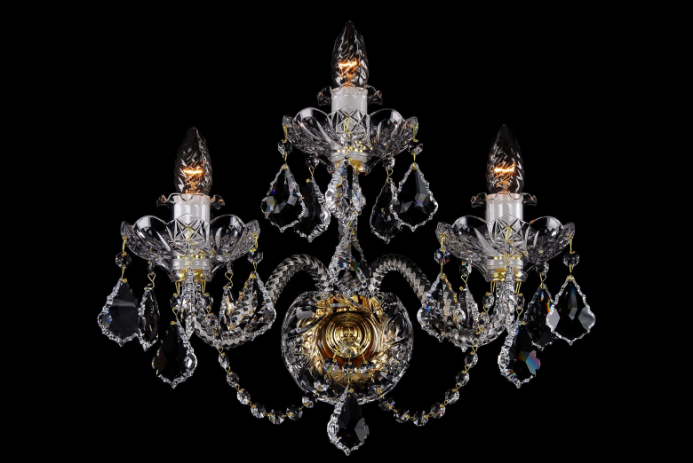 A three-arm neutral crystal wall lamp ornamented with Swarovski trimmings.