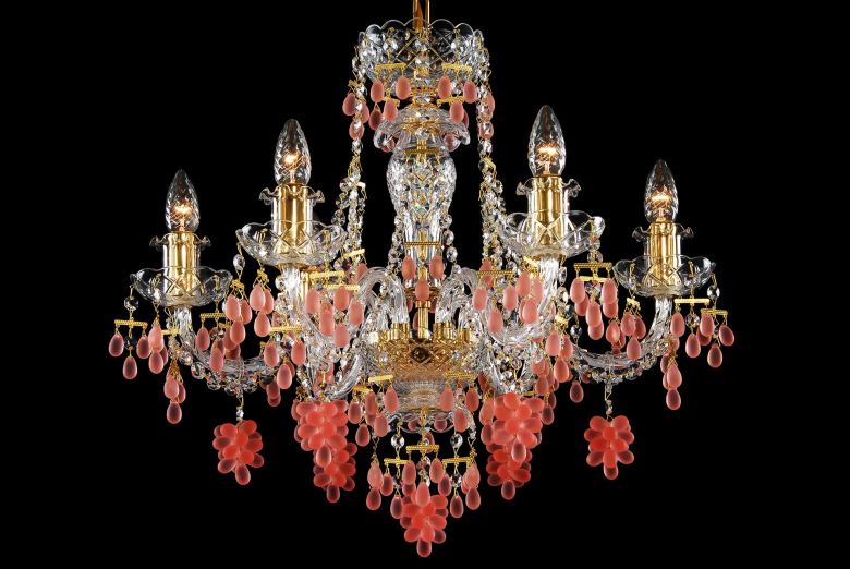 A six-arm crystal chandelier with gold coloured metal decorated with grape drops.