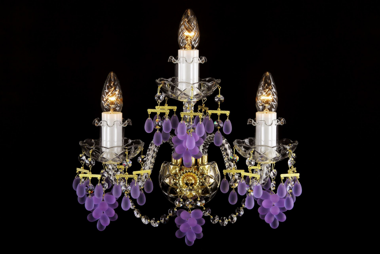 A three-light crystal wall lamp ornamented with grape-shaped trimmings.