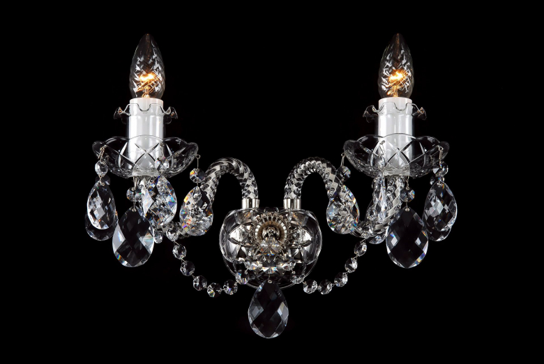 A two-arm crystal wall lamp decorated with silver metal.