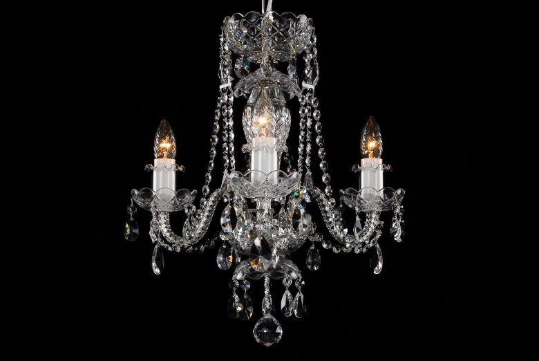 The smallest crystal chandelier decorated with silver coloured metal.