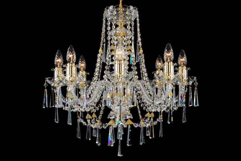An eight-arm crystal chandelier with gold coloured metal ornamented with long trimmings in the shape of a hoof.