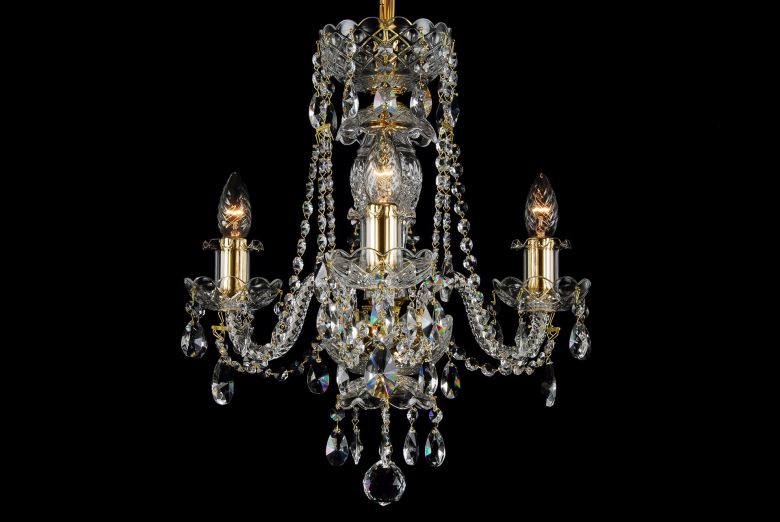 The smallest crystal chandelier decorated with gold coloured metal.