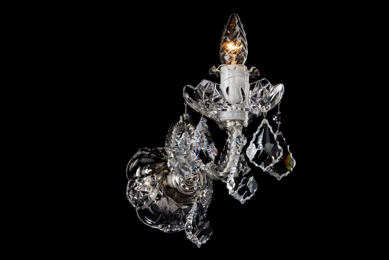 The smallest one-arm clear crystal wall lamp ornamented with Swarovski trimmings.