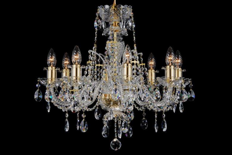 A crystal chandelier with gold coloured metal decorated with a high crown.