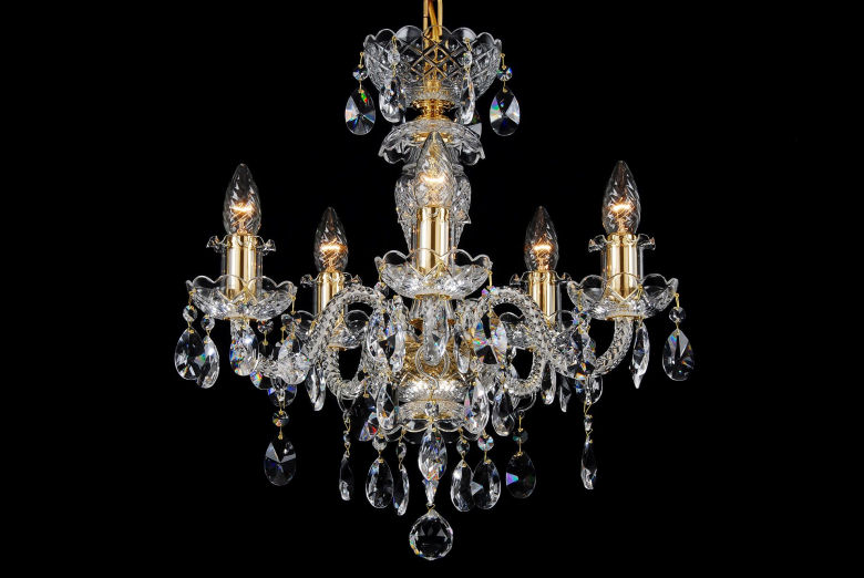 A small five-arm crystal chandelier decorated with golden metal.