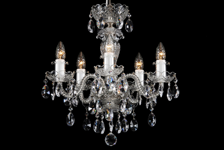 A small five-arm crystal chandelier decorated with silver coloured metal.