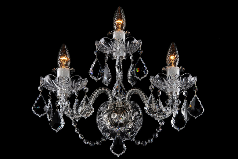 A three-arm crystal wall light ornamented with Swarovski trimmings.