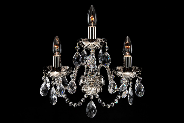 A three-arm silver coated crystal wall lamp.