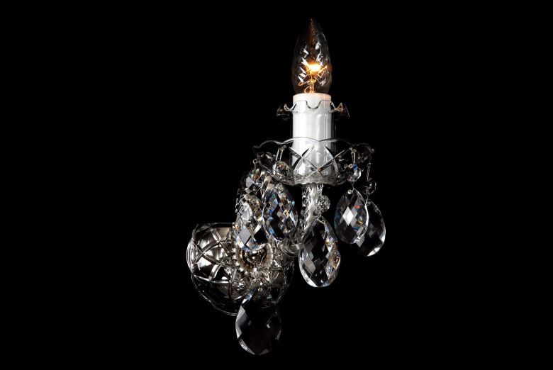 The smallest crystal wall lamp decorated with silver coloured metal.