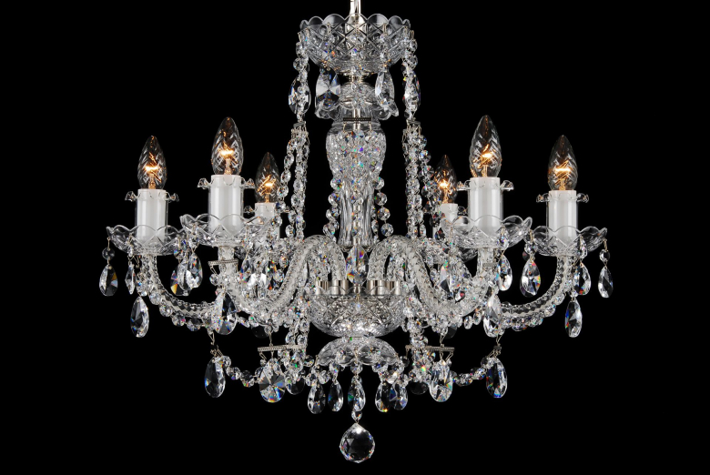 A six-arm chandelier decorated with silver coloured metal and crystal chains.