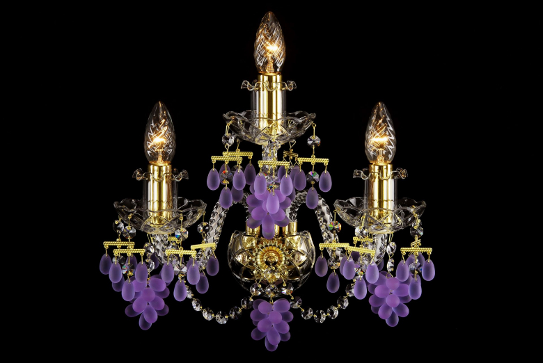 A three-arm crystal wall lamp ornamented with grape-shaped trimmings.