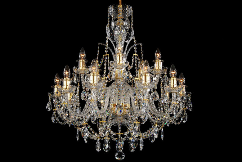 A fifteen-arm crystal chandelier with a crown and golden metal parts.