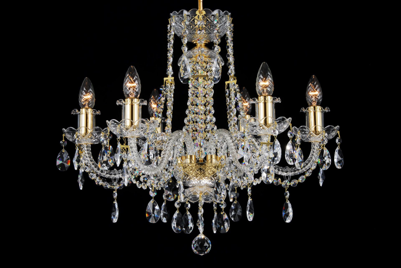 A six-arm chandelier decorated with gold coloured metal and crystal chains.